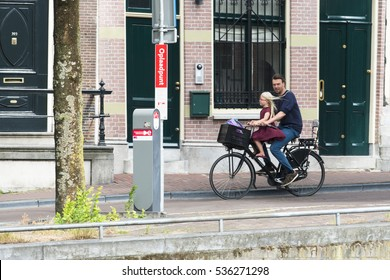 AMSTERDAM, NETHERLANDS - JULY 8, 2015: A man on a bicycle with a girl sitting in front, strolling through one of the streets of the city.