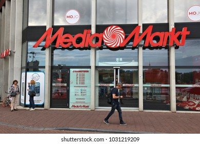 AMSTERDAM, NETHERLANDS - JULY 8, 2017: People walk by Media Markt store in Amsterdam. Media Markt is the largest consumer electronics store chain in Europe.