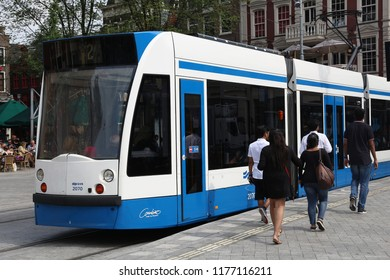 AMSTERDAM, NETHERLANDS - JULY 8, 2017: People ride the GVB electric tram (Combino model made by Siemens) in Amsterdam, Netherlands. GVB serves 211 million rides annually.