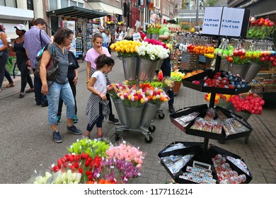 AMSTERDAM, NETHERLANDS - JULY 8, 2017: People visit the flower market (Bloemenmarkt) in Amsterdam, Netherlands. Bloemenmarkt is the famous flower market floating on canal Singel.