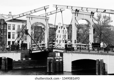 AMSTERDAM, NETHERLANDS - JULY 8, 2017: People visit Magere Brug (The Skinny Bridge) in Amsterdam, Netherlands. Amsterdam is the capital city of The Netherlands.