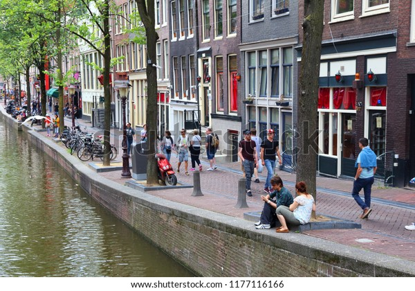 AMSTERDAM, NETHERLANDS - JULY 8, 2017: People visit Red Light District in Amsterdam, Netherlands. Amsterdam is notable for its relaxed laws towards prostitution.
