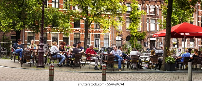 AMSTERDAM, NETHERLANDS, JULY 9  2016. People is relaxing and have a drink on a terrace along the canal in Amsterdam, style of life in Amsterdam, Netherlands.