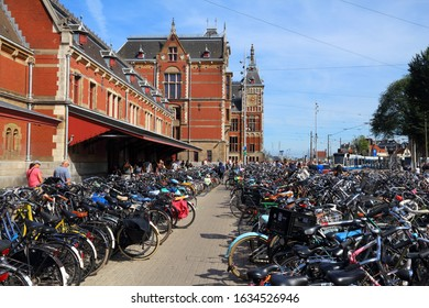 AMSTERDAM, NETHERLANDS - JULY 9, 2017: People visit bicycle parking in front of Amsterdam Central Station (Centraal). Netherlands is extremely friendly towards bicycles.