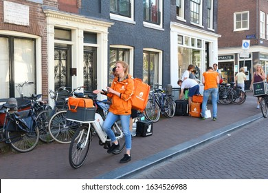 AMSTERDAM, NETHERLANDS - JULY 9, 2017: Uber Eats, Thuisbezorgd and Deliveroo food couriers wait in Amsterdam, Netherlands. Bicycle food delivery is popular in Amsterdam.