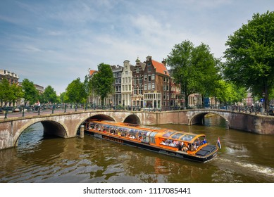 Amsterdam, Netherlands - June 1, 2018 : Orange boat of the Lovers Canal Cruises with tourists boating through the famous Keizersgracht canal intersection in Amsterdam