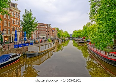 AMSTERDAM, NETHERLANDS - JUNE 12, 2016: Canal spring scene with historic houses and houseboats in peaceful morning.
