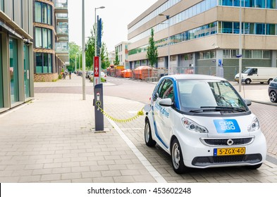 Amsterdam, The Netherlands - June 12, 2016: Car2Go Electric Car being Charged. Car2go is carsharing service available in Europe and North America. The Cars are user-accessed via a smartphone app