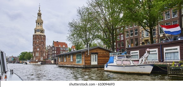 AMSTERDAM, NETHERLANDS - JUNE 13, 2013: Amsterdam scene with typical  traditional dutch old buildings and houseboats in the canal.