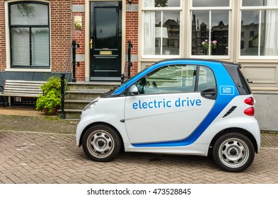 Amsterdam, The Netherlands - June 13, 2016: Car2Go Car Sharing Electrical Vehicle Parked in front a Brick House. Car2go cars are user-accessed wherever parked via a downloadable smartphone app.