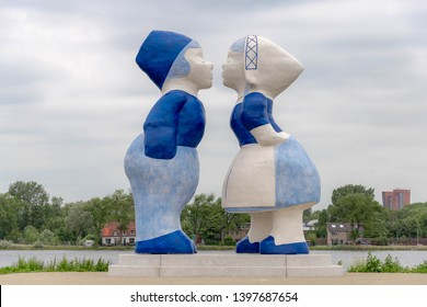 AMSTERDAM, THE NETHERLANDS - June 14, 2018: Large statue Dutch kissing couple XXXL along river, Feel the love in Amsterdam, Westelijk Havengebied, Holland.