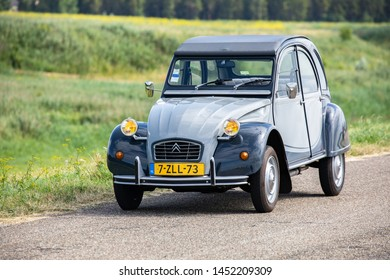 AMSTERDAM, NETHERLANDS - JUNE 14, 2019: A grey colored antique French oldtimer classic car Citroen 2CV Charleston with yellow head lights, is parked along the road