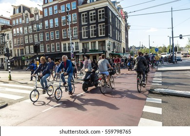 AMSTERDAM, THE NETHERLANDS - JUNE 16, 2016: People riding bicycles in historical part of Amsterdam in a beautiful summer day, The Netherlands on June 16, 2016