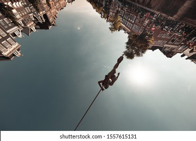 AMSTERDAM, NETHERLANDS - JUNE 17, 2019: Unidentified man entertains curious crowd, performs tightrope walking, also called funambulism - the skill of walking along a thin wire or rope, Holland