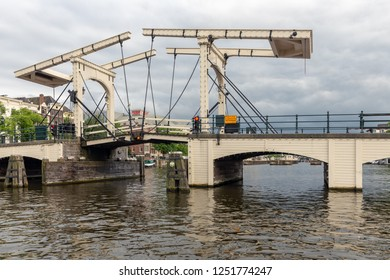 Amsterdam, The Netherlands - June 19, 2018: View at Magere Brug, famous bridge in Amsterdam Canals. At the background the Carre theatre