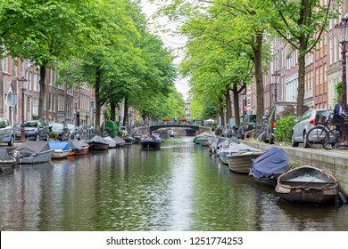 Amsterdam, The Netherlands - June 19, 2018: View at several moored sloops and sailing boat with passengers in Amsterdam Canal