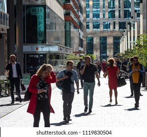 Amsterdam, The Netherlands - June 20, 2018: People with smartphone on the Amsterdam Zuidas, Netherlands.