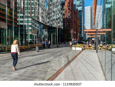 Amsterdam, The Netherlands - June 20, 2018: Woman with smartphone on the Amsterdam Zuidas, Netherlands, with tall office buildings.