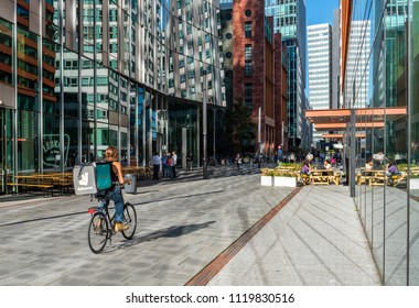 Amsterdam, The Netherlands - June 20, 2018: Deliveroo man on bicycle on the Amsterdam Zuidas, Netherlands, with tall office buildings.
