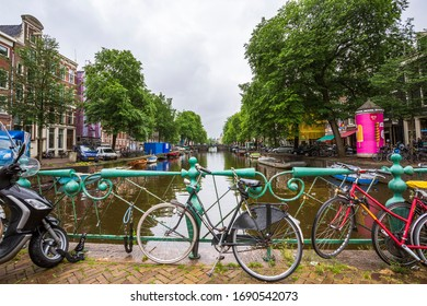 Amsterdam, Netherlands, June 2016 - Many colored bicycles leaning agains the rail on a bridge in one of Amsterdam's canals in a rainy day.