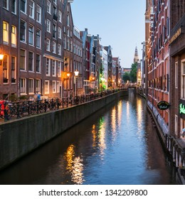 AMSTERDAM, NETHERLANDS - JUNE, 2018: Amsterdam cityscape along one of cannals and the De Oude Kerk Tower at dusk