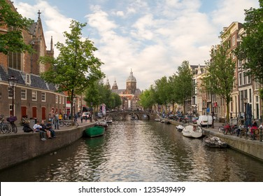 AMSTERDAM, NETHERLANDS - JUNE, 2018: Famous dutch canal and traditional old buildings in Red Light District of Amsterdam, Netherlands.