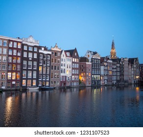 AMSTERDAM, NETHERLANDS - JUNE, 2018: Traditional dutch houses on canal in Amsterdam and Oude Kerk tower in distance, Netherlands. The Oude Kerk is Amsterdam's oldest building founded circa 1213.