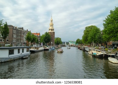 AMSTERDAM, NETHERLANDS - JUNE, 2018: View to the Montelbaanstoren tower and boats at one of canal of Amsterdam, Netherlands