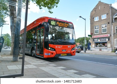 Amsterdam / Netherlands - June 2019: Red R NET bus at bus stop. All public transport systems in Amsterdam are electric including the bus services that run through the city.