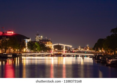 AMSTERDAM, THE NETHERLANDS - June 21, 2018: Amsterdam at night with view of Magere Brug (Skinny Bridge) at night, Cityscapes view lighted canal bridges,  Netherlands.