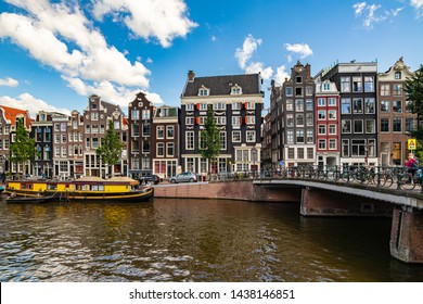 Amsterdam, Netherlands - June 21, 2019: View of the canals in Amsterdam. People enjoying the sunny weather.