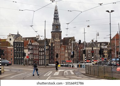 AMSTERDAM, NETHERLANDS - JUNE 25, 2017: View to the belfry tower (XVI century) on the Oude Kerk church and other historical buildings from intersection of Damrak and Prins Hendrikkade streets.