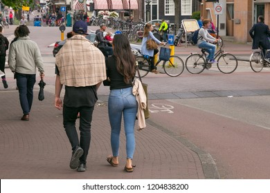 AMSTERDAM, NETHERLANDS - JUNE 25, 2017: An unknown young couple walking one of the streets in the center of Amsterdam.
