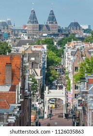 Amsterdam, The Netherlands, June 26, 2018: View from above on street and Skinny Bridge (Magere Brug) in the  morning with traffic and in the background Rijksmuseum Amsterdam.