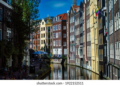 Amsterdam, Netherlands - June 27, 2019: A tranquil canal with a row of traditional brick houses and a rainbow flag in Amsterdam, the Netherlands