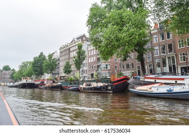AMSTERDAM, NETHERLANDS, JUNE 3, 2016: Water level view from one of the canals of one of the historic buildings and boats in Amsterdam, Netherlands on June 3, 2016.