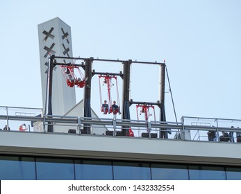 Amsterdam, Netherlands - June 3, 2019: people having fun in Europe's highest swing called 'Over the Edge' on A'dam Lookout observation deck. Swing located on top of the A'dam Tower Amsterdam North