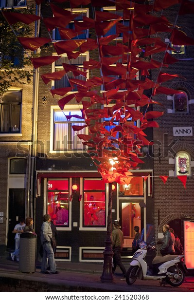 Amsterdam, The Netherlands - June 8, 2012: De Wallen or De Walletjes is the largest, and best-known, red-light district in Amsterdam and a major tourist attraction.