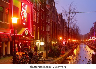 AMSTERDAM, NETHERLANDS - MARCH 10, 2013: Red-light district in Amsterdam. There are about three hundred cabins rented by prostitutes in the area.