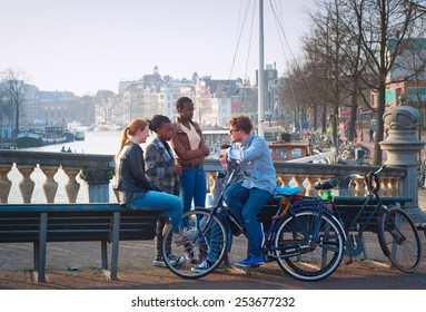 AMSTERDAM, NETHERLANDS - MARCH 10, 2104: Multicultural friends in conversation on Amsterdam street. About 177 different nationalities are residing in Amsterdam, most multicultural city in the world.