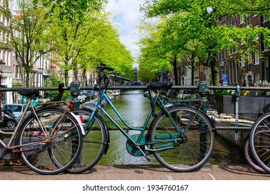 Amsterdam, Netherlands - March 13, 2021: Cycling in Amsterdam. Green bicycle locked and parked on the bridge placed on a canal. Amsterdam bicycles and canals.