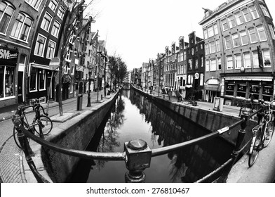 AMSTERDAM, NETHERLANDS, MARCH 16, 2013: Black and white photography of Amsterdam street with a river taken from a bridge with fish-eye lens