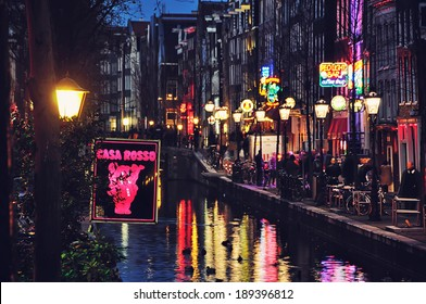 AMSTERDAM, NETHERLANDS - MARCH 16, 2014: Night view of Red - light district, where is a concentration of sex shops, strip clubs, adult theaters, etc. The sign of famous Casa Rosso erotic Theater