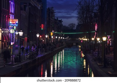 AMSTERDAM, NETHERLANDS - MARCH 16, 2014: Night view of Red - light district, where is a concentration of sex shops, strip clubs, adult theaters, etc.