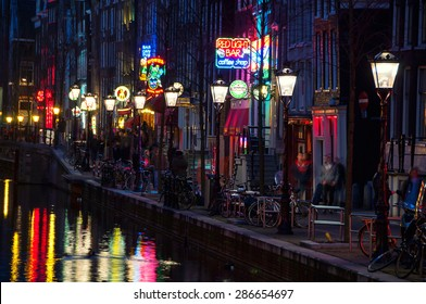 AMSTERDAM, NETHERLANDS - MARCH 16, 2014: Night view of Red - light district, where is a concentration of sex shops, strip clubs, adult theaters, etc. The sign of Red Light Bar coffee shop