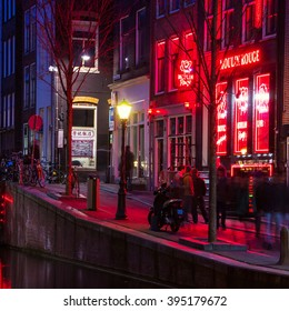 AMSTERDAM, NETHERLANDS - MARCH 16, 2014: Night view of Red - light district, where is a concentration of sex shops, strip clubs, adult theaters, etc. Facade of Moulin Rouge Theater