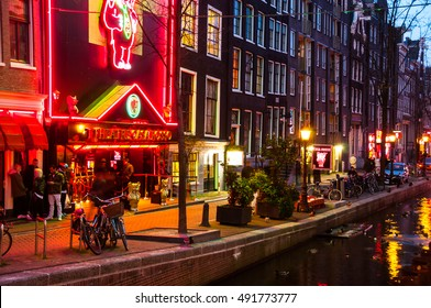 AMSTERDAM, NETHERLANDS - MARCH 16, 2014: Night view of Red - light district, where is a concentration of sex shops, strip clubs, adult theaters, etc. Entrance to Theater Casa Rosso