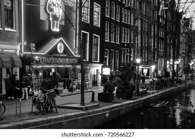 AMSTERDAM, NETHERLANDS - MARCH 16, 2014: Night view of Red - light district, where are sex shops, strip clubs, adult theaters. Entrance to Theater Casa Rosso in Amsterdam. Black and white