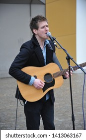 AMSTERDAM, NETHERLANDS / NETHERLANDS - MARCH 19 2010: A british musician with amplified acoustic guitar and microphone is busking on the street of Amsterdam.