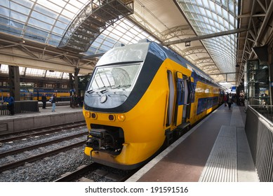 AMSTERDAM, NETHERLANDS - MARCH 19, 2014: Yellow train stands on the central railroad station in Amsterdam